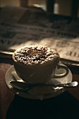 A cup of cappuccino in front of a newspaper on table