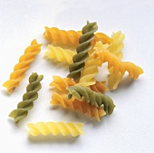 Mixed pasta spirals (Eliche) on a grey background