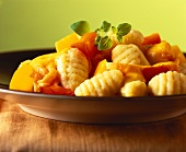 Gnocchi with pumpkin and peppers on plate