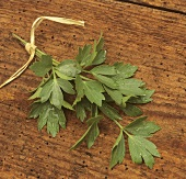 A bunch of lovage with drops of water on wooden background