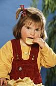 Small girl eating potato crisp