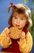 Small girl eating a flat bread