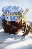 Raspberry jam in a jar with cinnamon stick and star anise