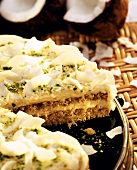 Coconut cake, a piece cut, with coconut crisps and pistachios