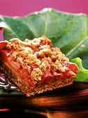 A piece of rhubarb crumble cake on a rhubarb leaf