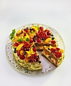 Colourful fruit gateau with cream quark and chopped pistachios