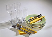 Glasses, pile of plates, cutlery & yellow paper napkins