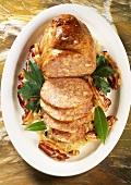 Stuffed pig's stomach with bacon & sauerkraut on platter