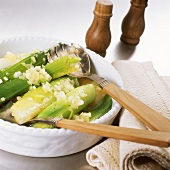Leeks in sherry with onions in a bowl with salad servers