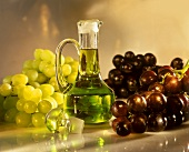 Grape seed oil in bottle, surrounded by fresh grapes