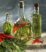 Three bottles of herb vinegar with sage, rosemary & thyme
