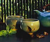 Two tea bowls and teapot; lemon balm leaves