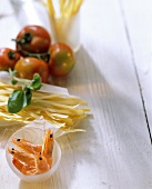 Still life with shrimps, noodles, tomatoes and basil