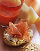 Roll with parma ham, cream cheese, melon; tomato juice