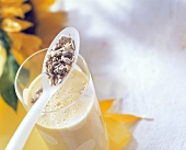 Mango ayran with sunflower seeds in glass and on spoon