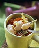 White bean salad with celery and tomatoes in cup