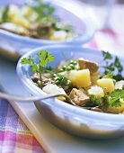 Vegetable stew with pork in blue soup plates