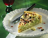 A piece of bean tart with bacon, cheese & pumpkin seeds