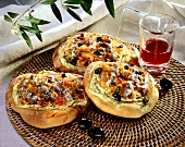 Onion flatbread with anchovies, olives & tomatoes; wine glass