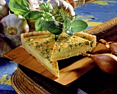 French herb tart on wooden platter; garlic, herbs