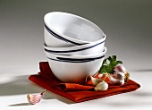 Three Asian bowls on fabric napkin with garlic