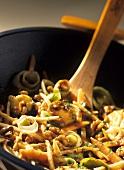 Sweet & sour winter vegetables & walnuts in wok, wooden spoon