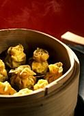 Steamed wontons in bamboo steamer in wok
