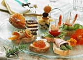 Various snacks and canapés on a glass plate