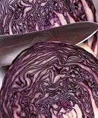 Red cabbage, cut into two halves, with knife (close-up)