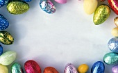 Coloured chocolate eggs, grouped round edge of picture