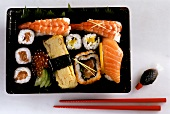 Various sushi and maki in a plastic bowl