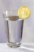 A glass of water with a slice of lemon