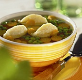 Clear vegetable soup with dumplings in yellow bowl