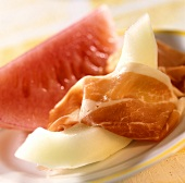 Melons with raw ham on a plate
