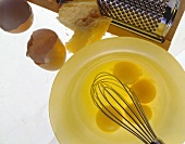 Broken raw eggs, egg shells and parmesan with grater