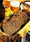 Sliced party loaf in bread basket; beer