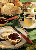 Breakfast with bread, jam and cheese, coffee, bread basket