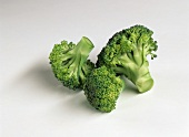 Three broccoli florets on white background