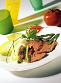 Roast beef slices with green asparagus & chicory on plate