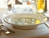 A plate of grape soup on laid table
