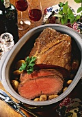 Roast beef with potatoes in roasting dish; red wine