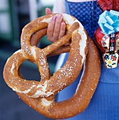Woman in blue German costume holding two large pretzels