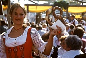 Young woman with giant pretzel in her hand at Oktoberfest