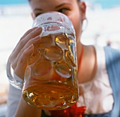 Young woman drinking beer at Oktoberfest