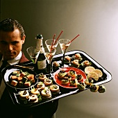 Waiter serving elegant snacks and champagne on a tray