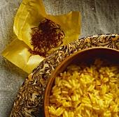 Saffron rice in a bowl with saffron strands on paper