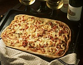 Alsatian pizza (Flammenkuchen) on baking sheet; white wine