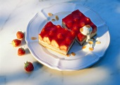 Two strawberry slices with cream and flaked almonds
