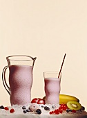 Ice-cooled berry shake in glass and jug