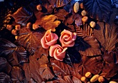 Still life with marzipan roses, chocolate leaves and nuts